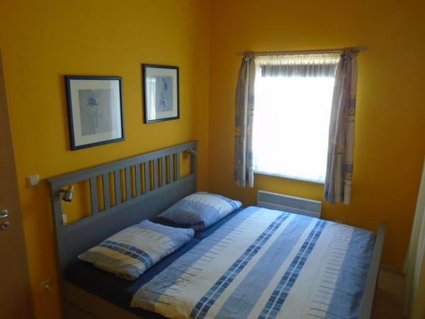 Schlafzimmer mit Doppelbett 180x200 cm, am Fenster befindet sich ein Verdunklungsrollo