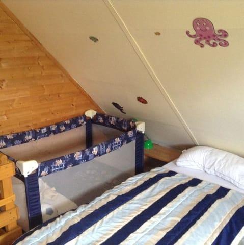 Im oberen Schlafraum bieten wir neben einem Doppelbett und einem separaten Bett ein Reisebett für Kleinkinder.