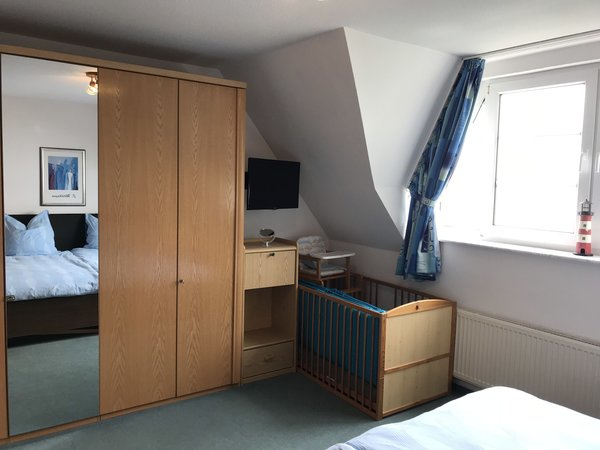 Elternschlafzimmer mit LCD - TV und Kinderbett