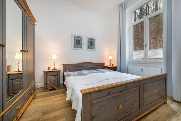 Das Bett bietet Schlafkomfort auf 2x2m. Das Fenster hat Gardinen und Plissees.
