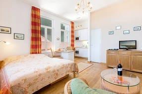 Das Foto zeigt den Schlafbereich und den Blick Richtung Küchenzeile.