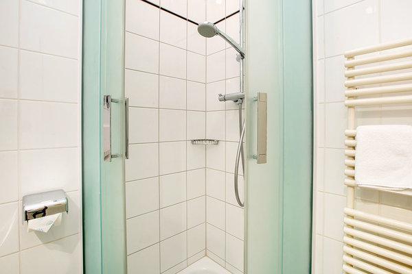 ... mit Dusche, Handtuchtrockner und WC.