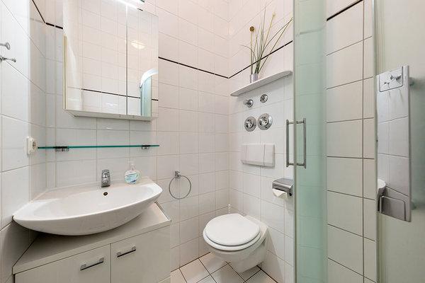 Das Bad bietet Ihnen Dusche, Waschbecken und WC.
