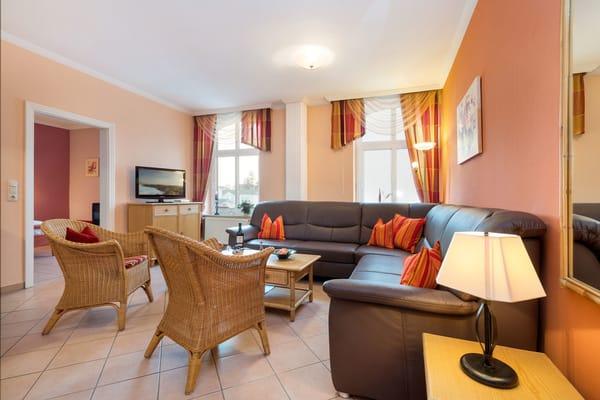 Im großzügig geschnittenen Wohnzimmer ist eine komfortable Sitzlandschaft mit Schlaffunktion vorhanden.