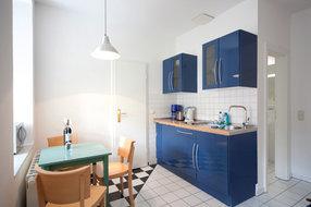 Die Küchenzeile ist ausgestattet mit 2-Platten-Herd, Kühlschrank, Mikrowelle, Kaffeemaschine, Toaster und Wasserkocher.
