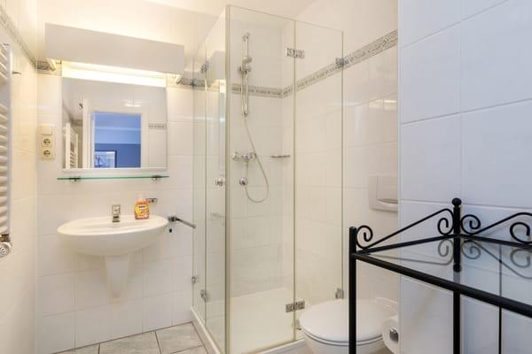 Das Bad hält Echtglasdusche und WC für Sie bereit.