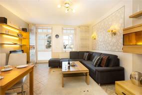 Blick Richtung Wohnlandschaft im Wohnzimmer. Die Couch bietet Platz zum Schlafen für 2 Personen. Im App. steht Ihnen WLAN kostenfrei zur Verfügung.