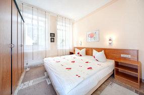 Das Schlafzimmer mit Doppelbett und großem Schrank.