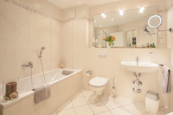 Das große Badezimmer hat Badewanne, WC, Fön und Dusche.