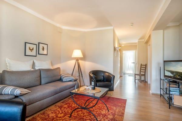 Blick durch den Flur zum Eingangsbereich. Rückwärtig tritt man aus der Wohnung auf einen überdachten Laubengang/Gemeinschaftsbalkon.