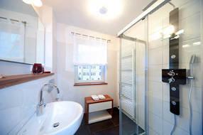 Oben im Bild sehen Sie das Bad mit Wellnessdusche, Waschtisch und WC. Rechts im Bild ist das Gäste-WC abgebildet.