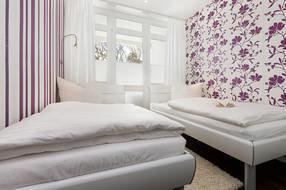 Das zweite Schlafzimmer hält zwei Einzelbetten mit Leseleuchten und einen Kleiderschrank bereit. Im Bild sehen Sie auch den Austritt zum Balkon.