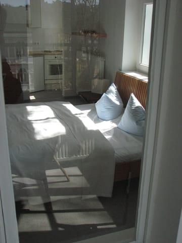 Blick vom Wintergarten in das Appartement D302. Das Licht spiegelt die Ausssicht auf die andere Straßenseite.