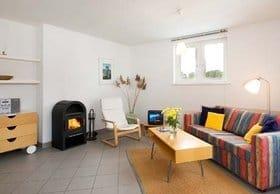 Wohnen unterm Dach: Das Wohnzimmer hat eine Kaminecke und ein Sofa, das sich auch als Bett nutzen lässt.