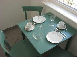 Der kleine Esstisch steht in der abgeteilten Küche. Sie finden dort alles nötige, um Speisen fast wie zuhause zubereiten zu können - ganz unabhängig von Restaurantzeiten.