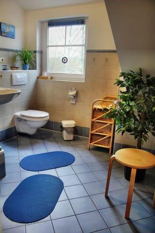 großes Badezimmer mit Fußbodenheizung, mit Dusche und Fenster in den Park Richtung Strand