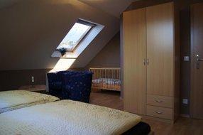 Schlafzimmer II im OG mit Kinderbett, Sitzbereich und Fernseher
