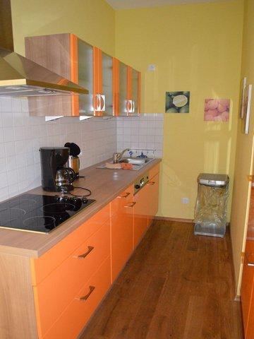 Küche mit Geschirrspüler, Kühlschrank, Kaffeemaschine und Wasserkocher