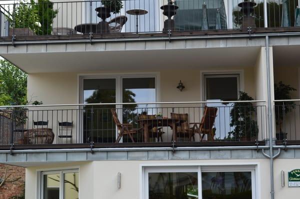 Detailansicht des großen Balkones mit Tisch und Stühlen zum Erholen.