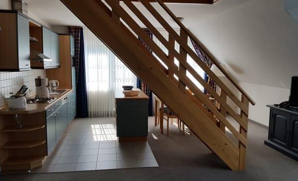 Blick vom Wohnbereich zum Essplatz und zur offenen Küche, im Vordergrund die Treppe zum oberen Schlafbereich