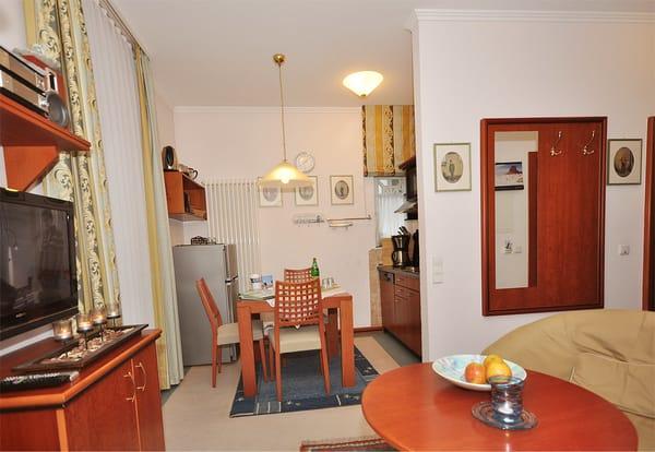 Blick vom Wohnzimmer Richtung Essbereich, der für vier Personen ausgestattet ist, und die Küchenzeile rechts,