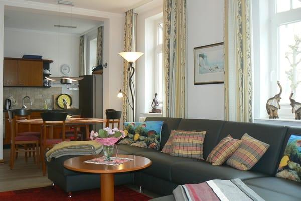 Wohnzimmer mit dem hochwertigen Leder-Sofa in Form einer großzügigen Wohnlandschaft mit Blick Richtung Essbereich und Küchenzeile
