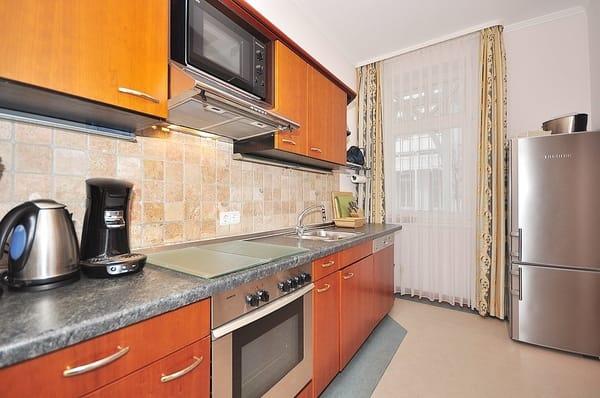 Küche mit komfortabler Ausstattung, u.a. einer großen Kühl- Gefrierkombination und separatem Zugang zum Balkon