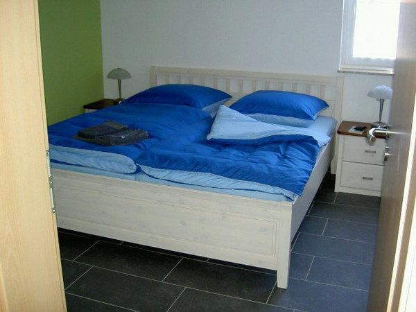 Schlafzimmer mit Doppelbett und dreitürigem Kleiderschrank