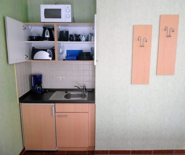 Pantryküche mit Küchengeräten und Geschirr