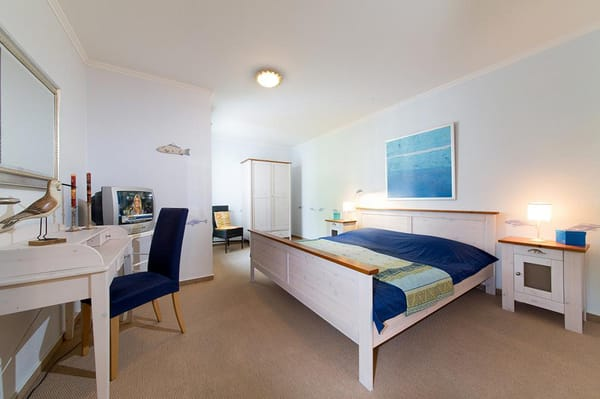 das liebevoll dekorierte Schlafzimmer mit Doppelbett, TV und Kleiderschrank