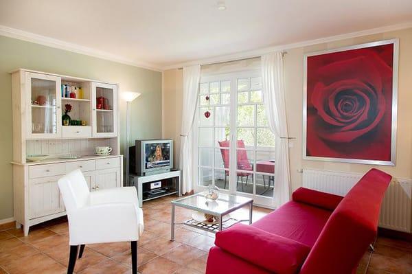 das sonnige Wohnzimmer mit einer Sofaecke, TV, Musik-Anlage und Zugang zum Balkon