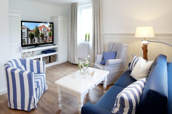 das modern eingerichtete Wohnzimmer mit einem Schlafsofa für die 3. und 4. Person, einem TV-Gerät mit integriertem Radio
