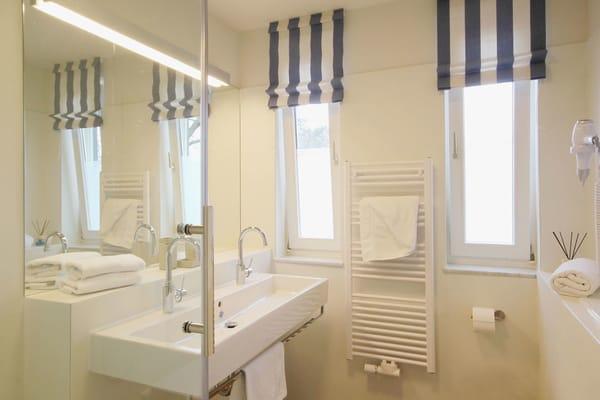 das Badezimmer mit WC, Doppelwaschtisch und Dusche