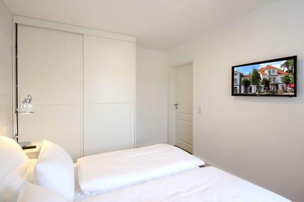 Schlafzimmer mit Kleiderschrank und zusätzlichem TV