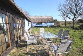 die gemütliche sonnige Terrasse am Haus im großen eingezäunten Bauerngarten zur alleinigen Nutzung, perfekt für Gäste mit Hunden