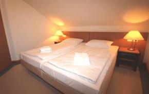 das Schlafzimmer unter der Dachschräge umfasst ein Doppelbett und einen Kleiderschrank