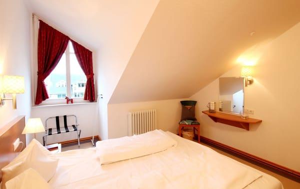 das komfortable Schlafzimmer unter der Dachschräge hat ein Doppelbett und einen Kleiderschrank