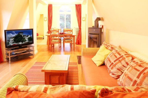 Wohnraum mit großem Ecksofa, Kamin, TV, Musikanlage, separatem Essplatz, Blick auf die Ostsee und Zugang zum Meerblick-Balkon