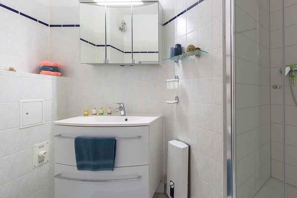 Badezimmer mit Toilette, Waschbecken und Spiegelschrank ...