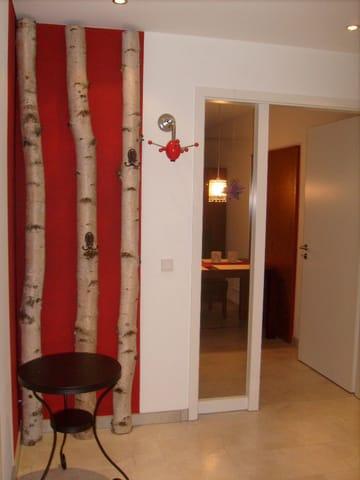 Der Eingangsbereich mit Blick in das Wohnzimmer. Rechts, hier nicht im Bild, schließt sich ein begehbarer Schrank mit Spiegeltüren an.