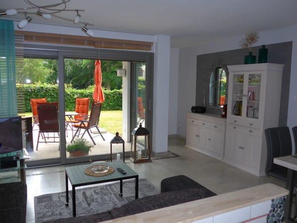 Wohnzimmer von der Küche aus gesehen. Rechts außerhalb des Bildes der Eßbereich. Die 3,60 m breite Fensterfront zur Terrasse mit Blick zum Eingangsbereich des Kurparks.
