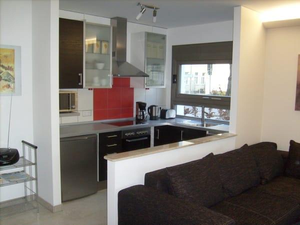 Die Küche ist durch eine halbhohe Wand vom Wohnzimmer abgetrennt. Sie hat ein separates Fenster zur Heinrich-Heine-Str. Die Küche ist mit den üblichen modernen technischen Geräten ausgestattet.