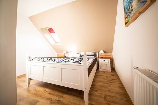 Das Schlafzimmer ist mit einem Doppelbett ausgestattet. Auf dem Schlafsofa im Wohnbereich können zwei weitere Personen bequem übernachten.