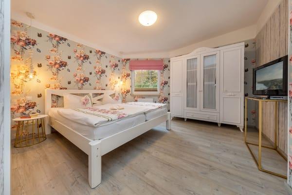 Schlafzimmer mit TV.  Das Doppelbett ist bequeme 1,80x2m breit. Plissee und Raffrollo am Fenster haben Verdunkelungsfunktion.