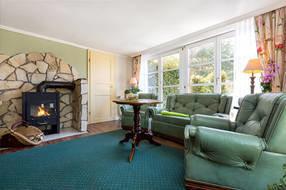 Das große Wohnzimmer hat eine komfortable Wohnlandschaft, einen Kaminofen, Flachbild-TV, Radio mit CD-Player und eine Küchenzeile.
