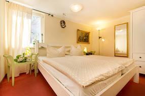Das Elternschlafzimmer hat ein großes Doppelbett und einen Schrank. Das Fenster ist mit einem Verdunkelungsplissee ausgestattet. Kinderbett und Hochstuhl werden gern kostenfrei bereitgestellt.