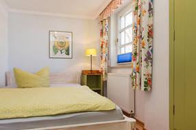 Das Bett im Kinderzimmer ist 1,40m breit. Das Fenster hat Plissee und Außenrollo für komplette Verdunklung.