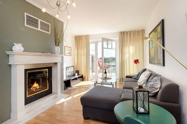 Hier sehen Sie das Wohnzimmer mit Blick zum Balkon. Der Kamin ist mit Holz beheizbar.