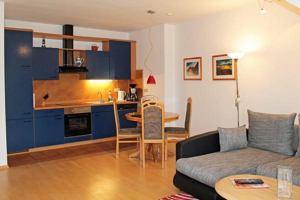 Komplett ausgestattete Küchenzeile mit Esstisch und Sitzgruppe