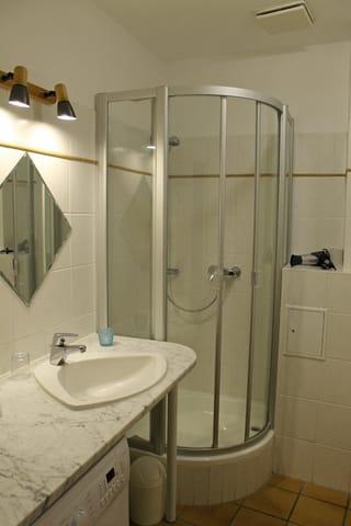 Das Badezimmer mit Dusche und WC und Waschmaschine